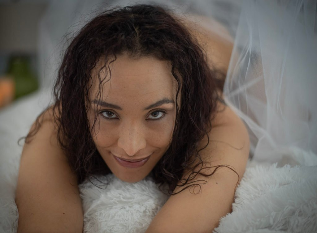 Boudoir photography girl grinning at camera on white sheets