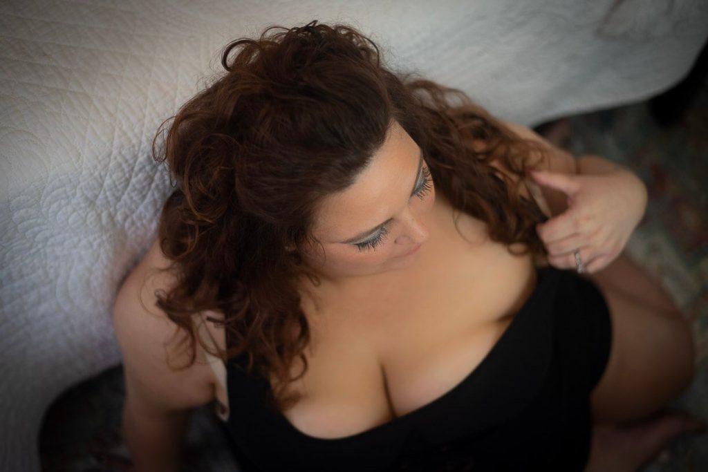 boudoir photography girl in black tank top sitting on the floor looking away