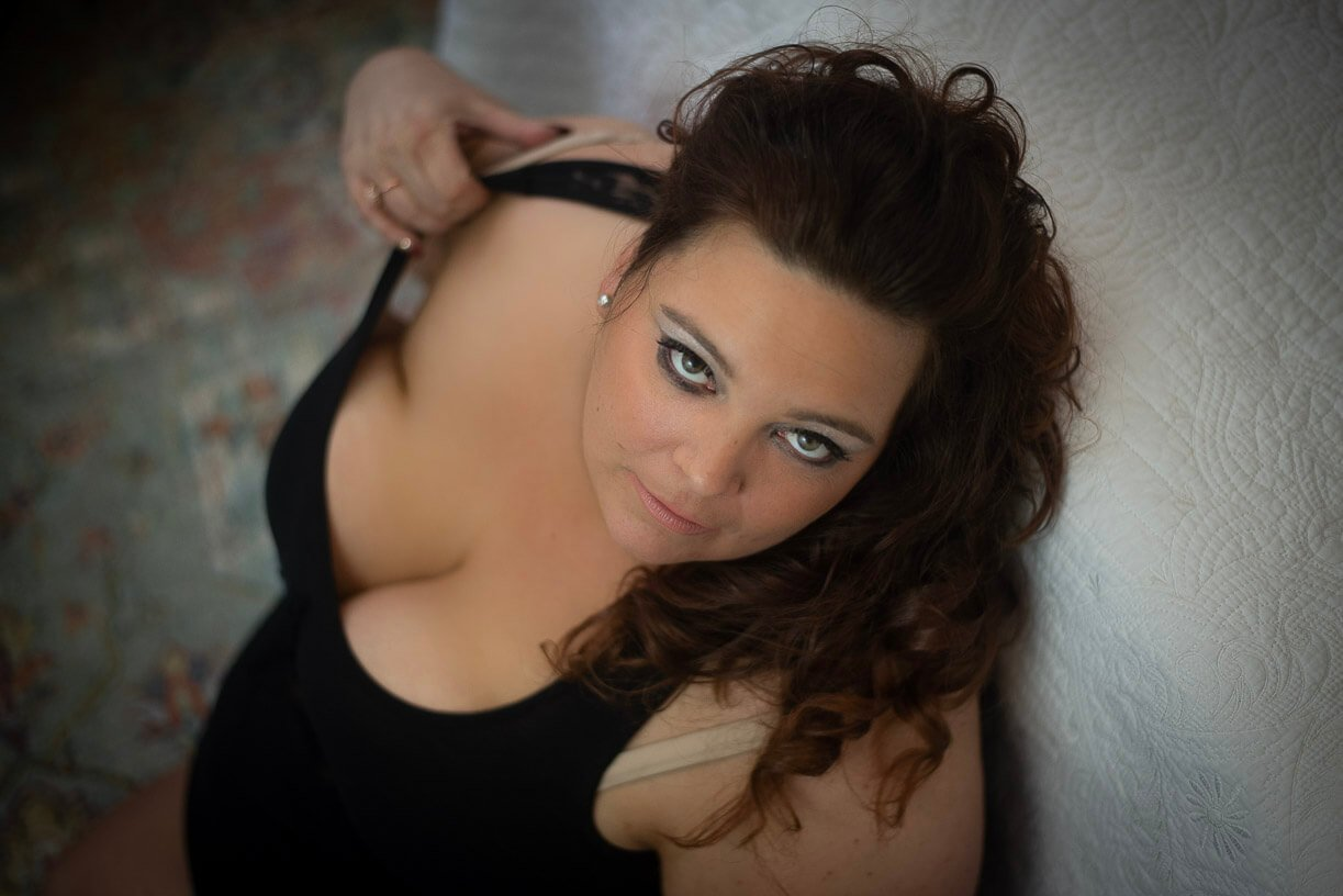 boudoir photography girl sitting on the floor wearing black tank top looking at the camera seductively