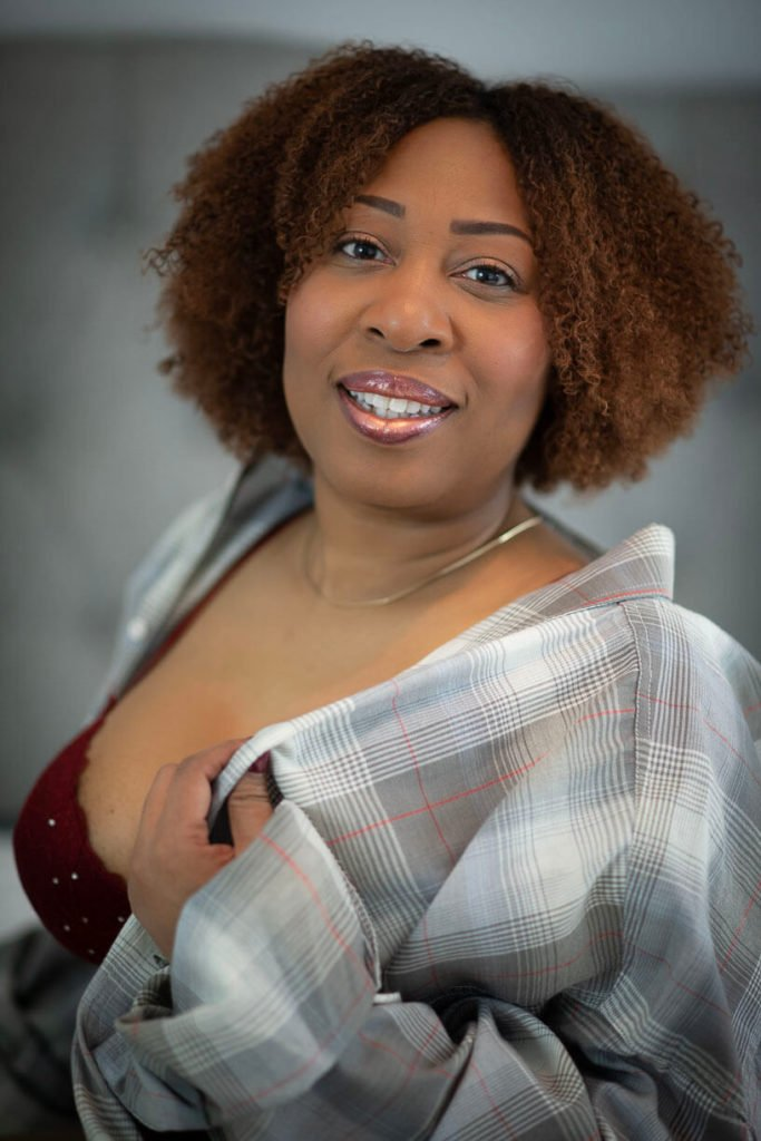 boudoir photography girl in red bra and oversized plaid shirt smiling