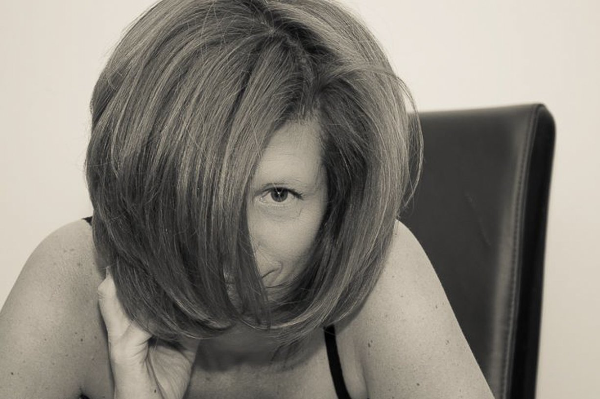 boudoir photography girl with hair over her face looking through her bangs at the camera